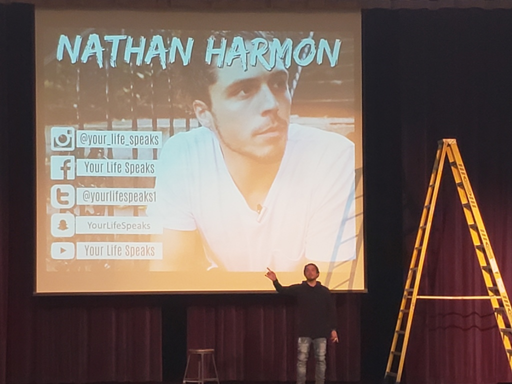Photo of Nathan Harmon on stage speaking