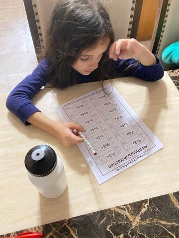 Photo of student doing her remote Math worksheet
