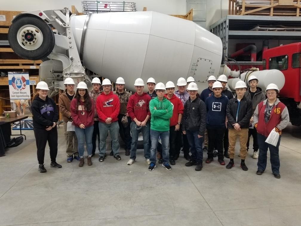 Photo of students standing in front of a cement truck